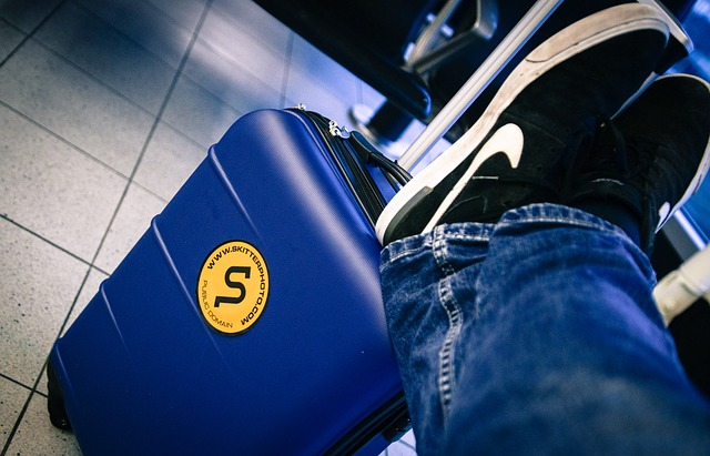 Person resting feet on luggage at airport